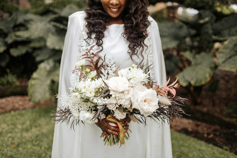 Bride wearing cape and holding bouquet