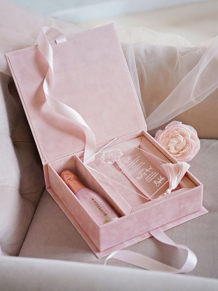 Velvet blush box with acrylic invite and event details in white type, mini bottle of champagne