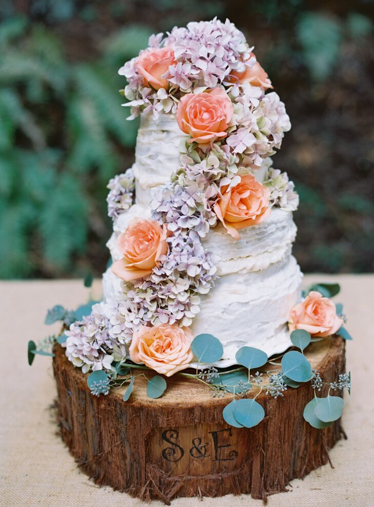 Shiloh's mom created a homemade three-tier white cake, covered in hydrangeas and peach-colored roses with scattered leaves at the bottom. Shiloh cut the redwood slab for the cake stand and carved his and Liz's initials onto the front.
