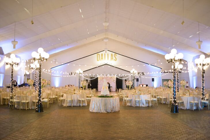 """The high white ceilings and brick floor in the Southfork Ranch reception hall was a truly magnificent setting for Blair and Alex's reception. Lanterns wrapped in string lights and overhead bistro lights set the tone for romance, and a big """"Dallas"""" in the backdrop gave the room a truly Texas feel."""