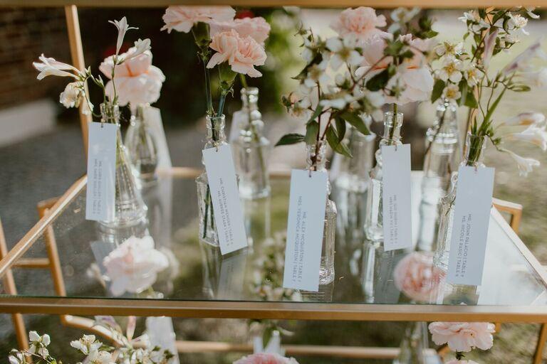 Escort cards attached to vintage bottles holding pink carnations