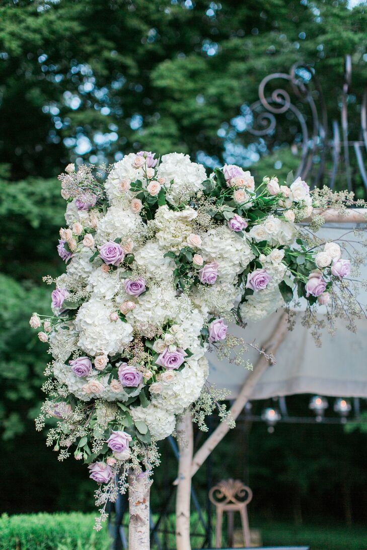"""The couple wed under a wooden flower-covered chuppah made by the groom's mother. """"Jesse is one of four siblings, and each corner of the chuppah had a sibling's and spouse's names embroidered,"""" Tara says."""