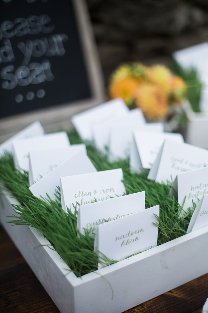 After cocktail hour guests moved inside to Winvian Gordon Brown House, a with a rustic wooden interior, for the reception. Bringing the beauty of the natural setting in, Arianne and Adam displayed their friends and family members' hand-lettered escort cards in a bed of fresh green grass that gave the charming, indoor space a note of vibrancy.