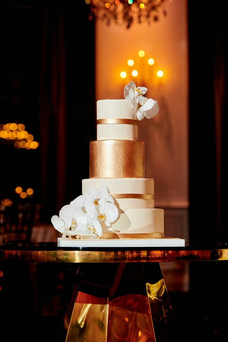 Gold-and-white wedding cake with orchids