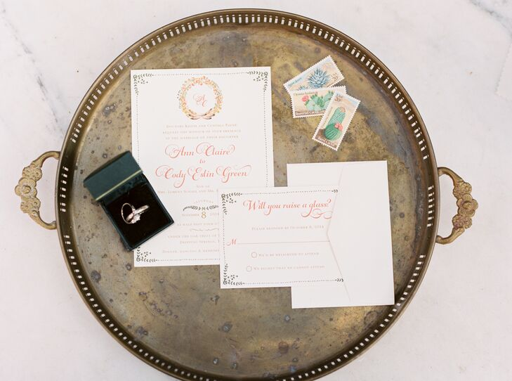 The white wedding invitations had elegant floral designs accenting its pages—from the wreath wrapped around Ann and Cody's initials at the top to the corners accented with leafy greens.