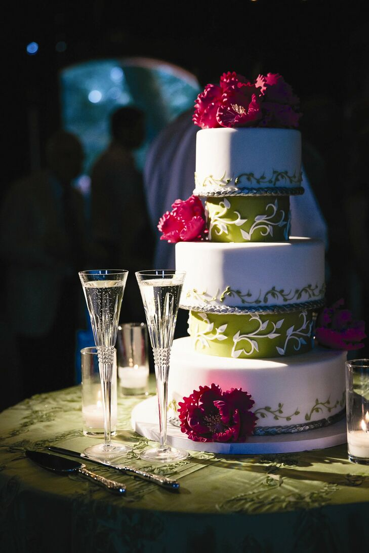 Layers of light green separated tiers of white fondant and green leaf motif designs in the couple's wedding cake.