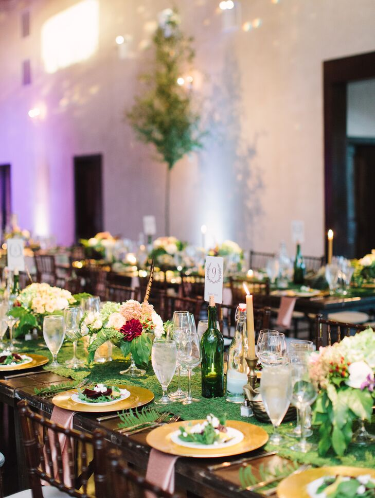 Inside the reception space, guests sat at dark wood dining tables set with gold plates and decorated with a green grass runner. A variety of moss, candles and colorful flower centerpieces covered the surface.