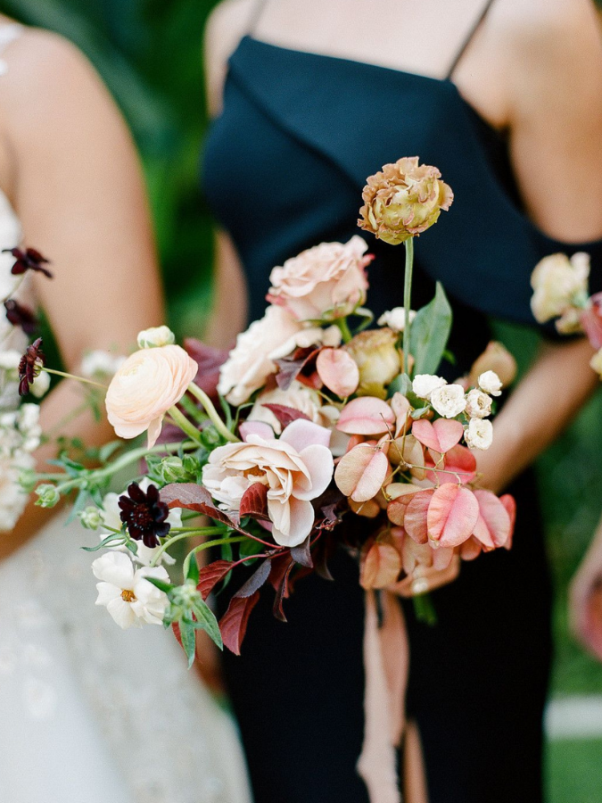 Bridesmaid in black dress holding wedding bouquet