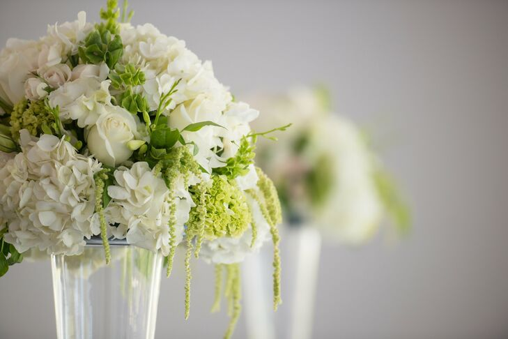 Dramatic floral arrangements in tall glass trumpet vases framed the ceremony. They consisted of white roses, hydrangeas, lisianthus, freesia, mini green hydrangeas, Bells of Ireland and hanging amaranthus.