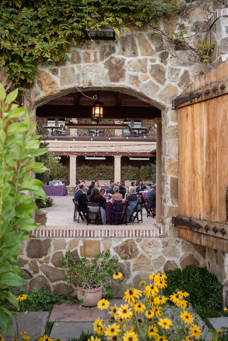 The open window revealed the outdoor reception space at Jacuzzi Family Vineyards in Sonoma, California, enclosed by stone walls covered with lush greenery. Guests sat at round dining tables that were covered in purple linens and decorated with floral centerpieces.