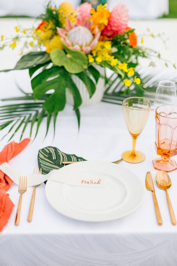 At the reception, tables were topped with centerpieces made with colorful blooms and glossy green fern leaf.  Brightly-hued glassware tied the table settings into the reception's oceanside location.