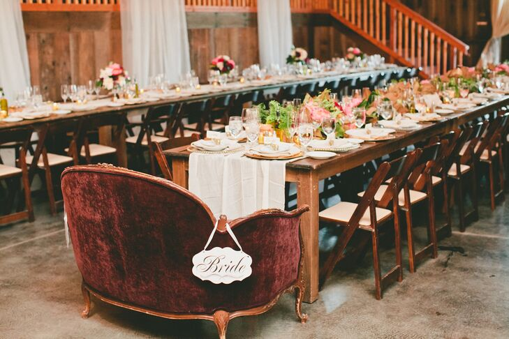 """Lydia and Brandon took their seats at the head of one of the long family-style dining tables at Olympia's Valley Estate in Petaluma, California. The newlyweds sat on the burgundy velvet love seat with """"bride"""" and """"groom"""" signs marking their territory."""