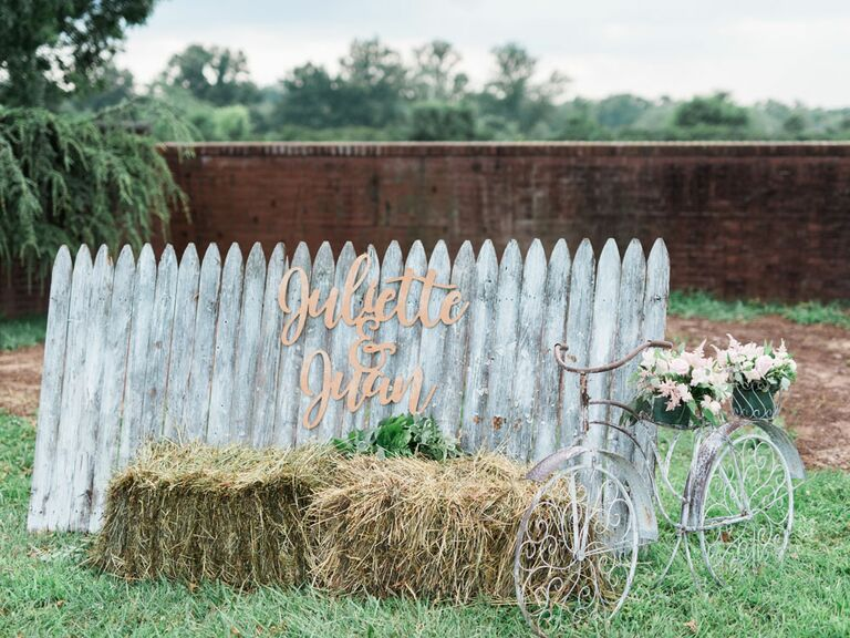 Shabby chic photobooth with distressed fence and hay bale next to vintage bike at barn wedding