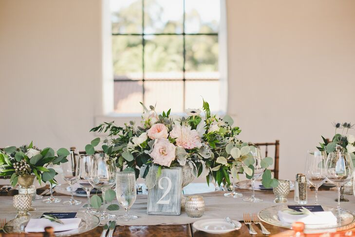 """Displayed atop light gray table runners dotted with brightly lit mercury-glass candleholders stood sophisticated stone bowl vases overflowing with eucalyptus, soft pink garden roses, dahlias and anemones. """"We used the stone vases and marbled table numbers to contrast the dark farm tables and chiavari chairs and tie the decor in with the lighter floral colors,"""" Ivette says."""