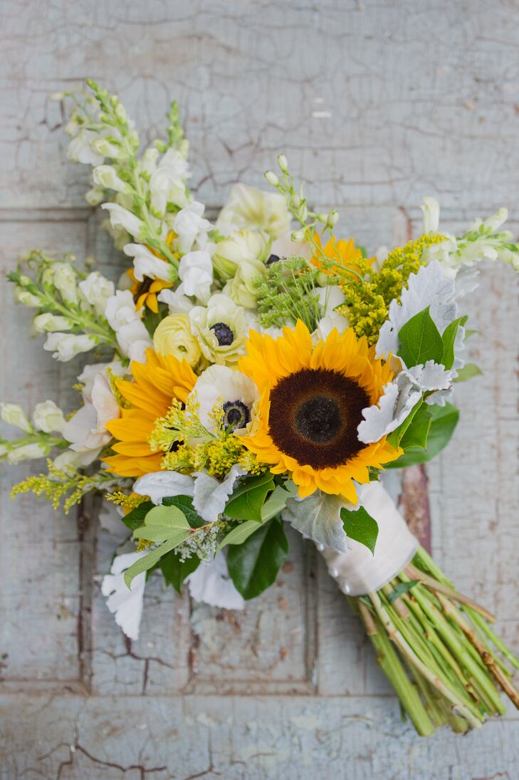 """""""I wanted the bouquets to look as though they were freshly picked and not overly arranged,"""" Caitlin says. Keeping this in mind, the couple's florist, Mark Bryan Designs, created a natural bouquet to go with Caitlin's lace wedding dress. Sunflowers, white anemones, yellow ranunculus, dusty miller, greenery and wildflowers were all wrapped in a white ribbon for the arrangement."""