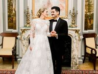 Bride in long sleeve beaded A-line wedding dress and groom in black tuxedo at regencycore wedding