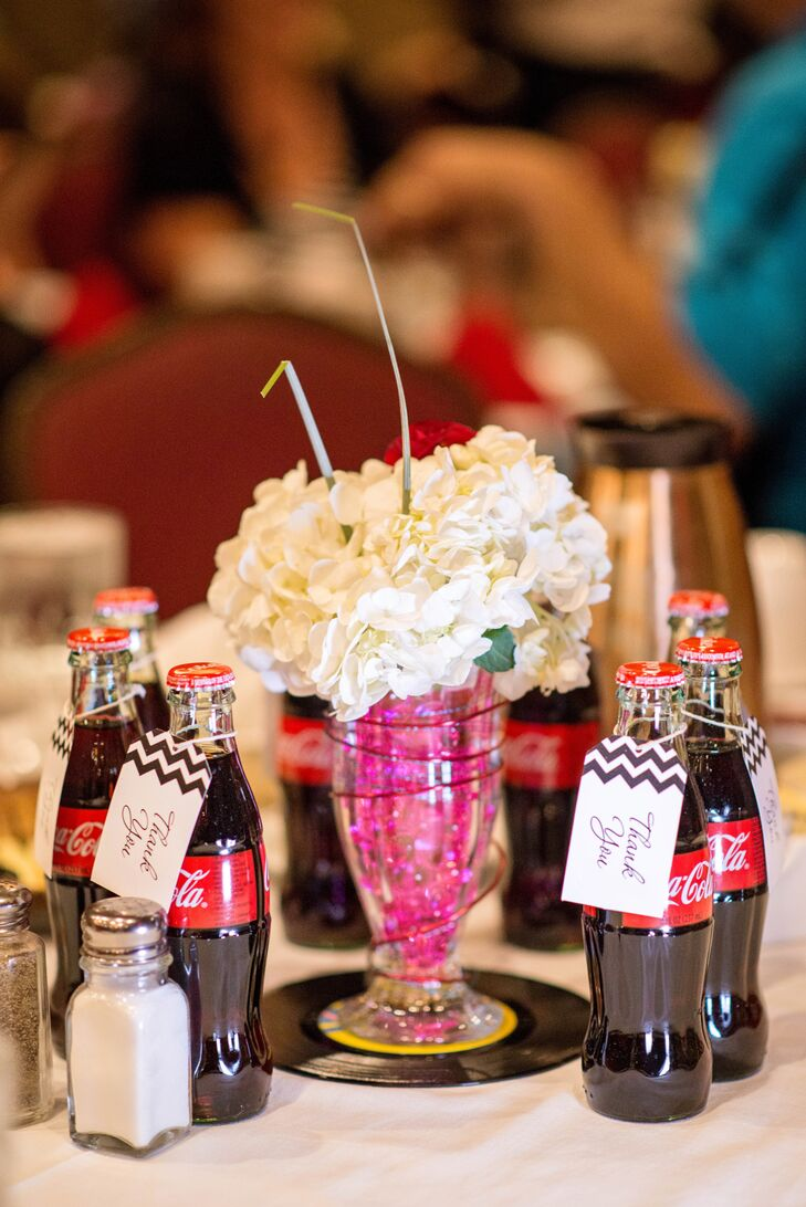 Leah and Cody came up with tremendously creative retro centerpieces with sundae glasses filled with white hydrangeas to look like whipped-cream-topped malted milkshakes. Glass coca-cola bottles doubled as both refreshments and retro-themed place cards.