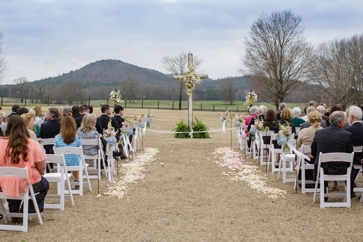 """""""Our florist, King's Garden [Susan Huff and Beth Jordan], knew the look we wanted and they just ran with it,"""" Mary Caroline says. On Mary Caroline and Forrest's wedding day, white and pink flower petals lined the aisle as arrangements of hydrangeas and delphiniums were hung alongside the first few rows of white folding chairs. Lush white and pink blooms also accented their wooden cross."""
