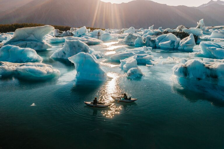 Couple kayaking amid icebergs