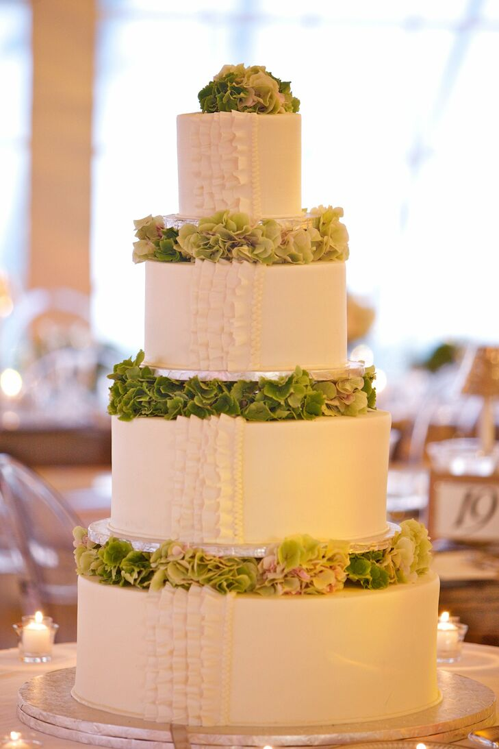 Fresh green hydrangeas accented Alex and Will's white-on-white cake, while a vertical row of pleated ribbons added texture to the simple confection.