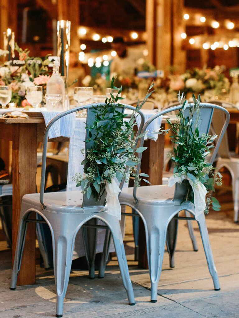 Industrial metal sweetheart chairs with sprigs of greenery at rustic barn wedding