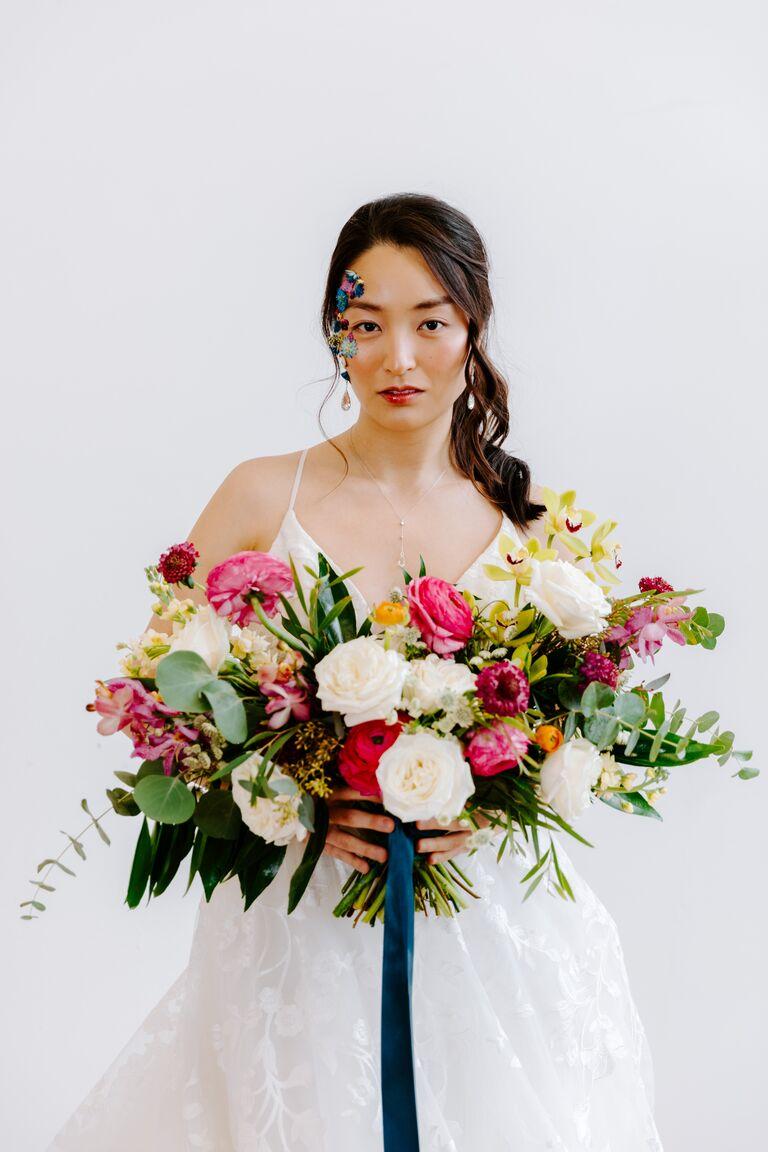 bride holding colorful wedding bouquet full of 2021 wedding colors hot pink yellow green white flowers and dark blue ribbons