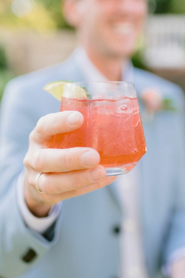 Bright Orange Signature Cocktail With Lemon Wedge
