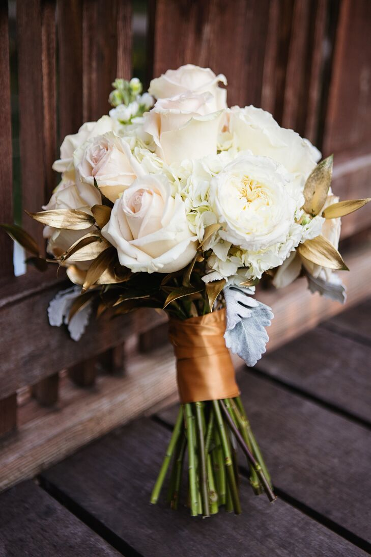 Christine carried white roses, hydrangeas, garden roses and dusty miller accents with spray painted gold leaves to match the ivory, blush and gold color palette.