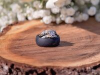 Black silicone wedding ring and metal wedding ring stacked on tree stump