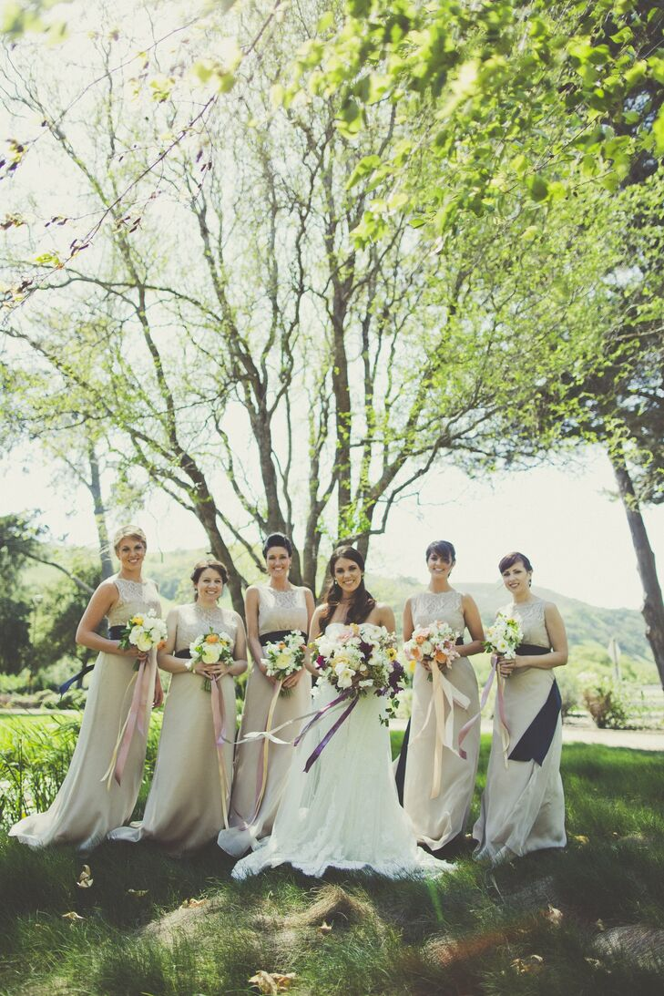 Lindsey's bridesmaids wore long, neutral dresses with a navy ribbon tied around the wait.