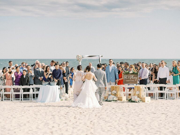 Guests watching bride walk down the aisle at outdoor beach formal wedding