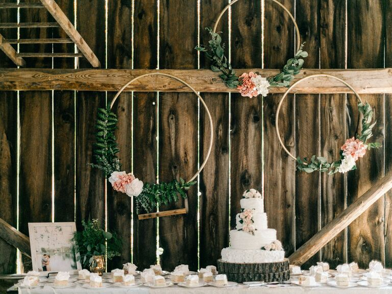 Rustic cake stand at barn wedding venue with floral circles and tree stump cake stand