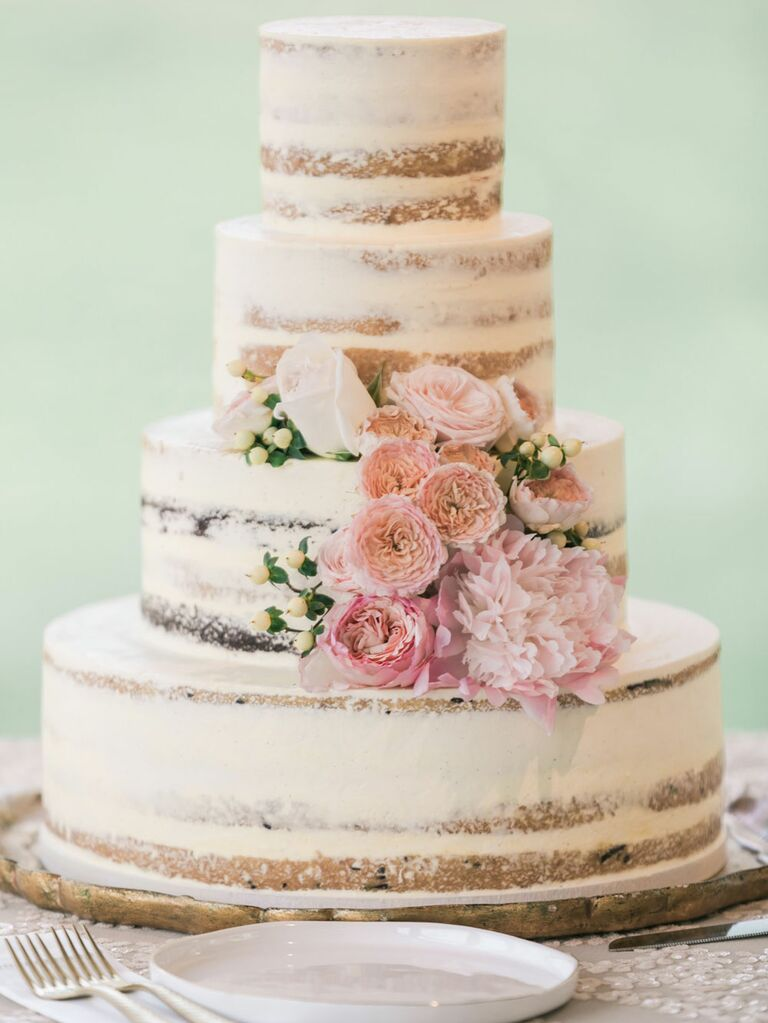 Four-tier rustic wedding cake with semi-naked icing and pink fresh flowers
