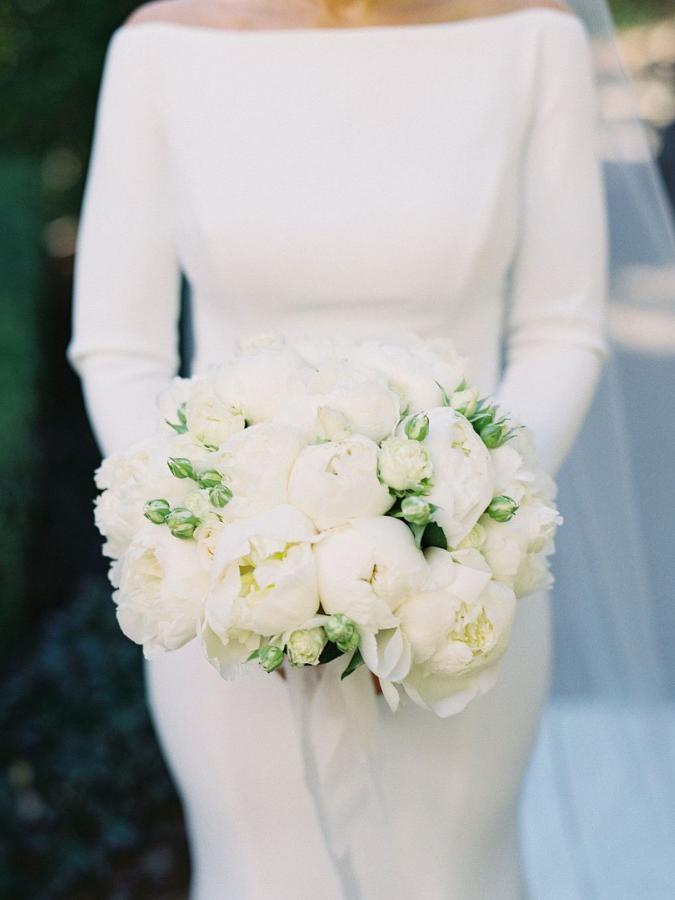Bride holding white peony bouquet