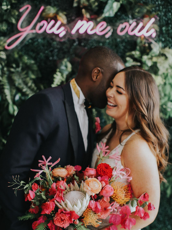 Couple laughing and holding pink bouquet