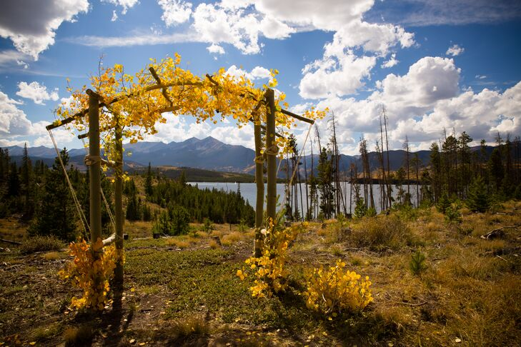 """""""The campground offered wonderful views across the reservoir and towards the Ten Mile Range,"""" Sarah says. The couple exchanged vows under a rustic wooden arbor adorned with yellow flowers and leaves."""