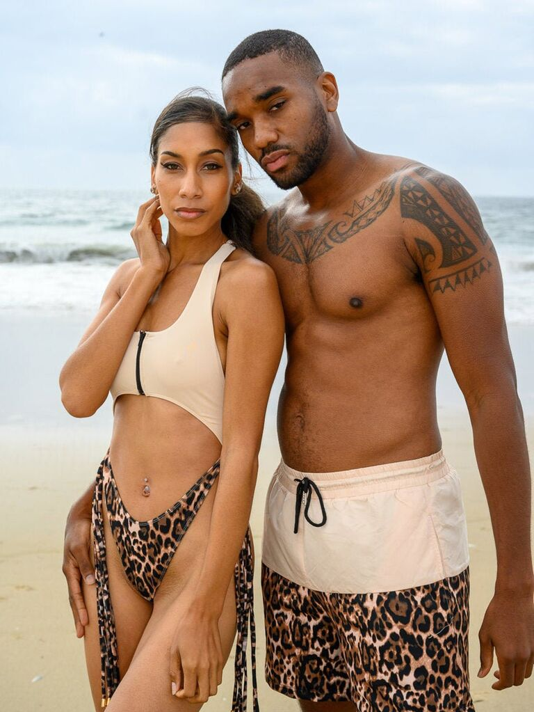 Couple wearing matching two-tone beige and leopard print one-piece and trunks