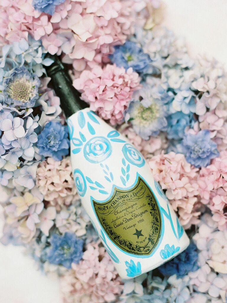 Blue and white champagne bottle on pink and blue hydrangeas at preppy-themed wedding