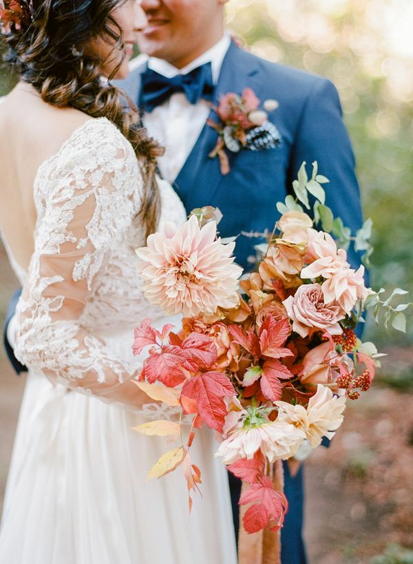 Bride hugging groom while holding fall wedding bouquet