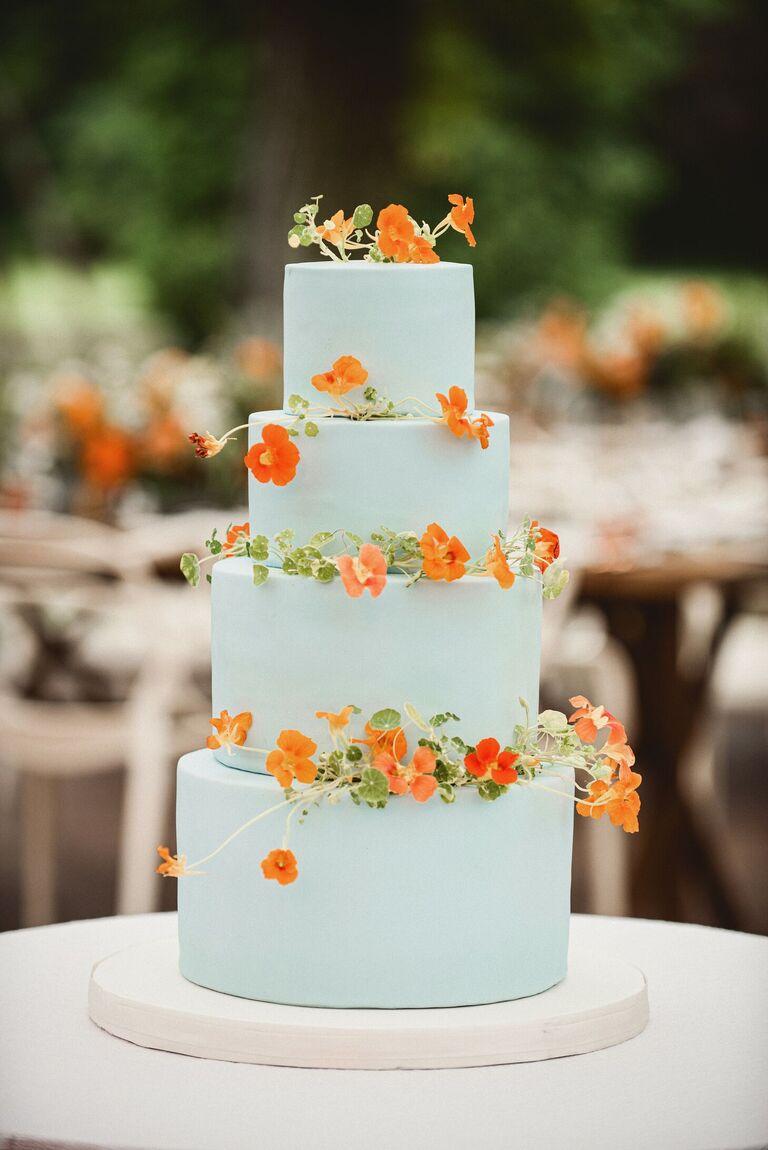 four-tier sky blue cake with orange nasturtiums