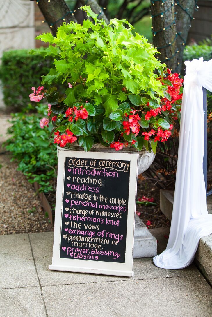 A large chalkboard sign detailed the program for the rose garden ceremony.