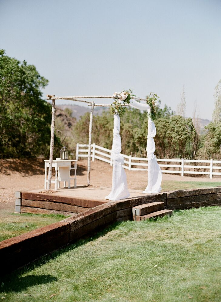 Jamie's father built a small stage for the ceremony using old railroad ties so that all of the guests would be able to see the ceremony with ease. An arbor made from birch branches and draped with flowing white fabric and soft floral arrangements added a romantic touch to the display.