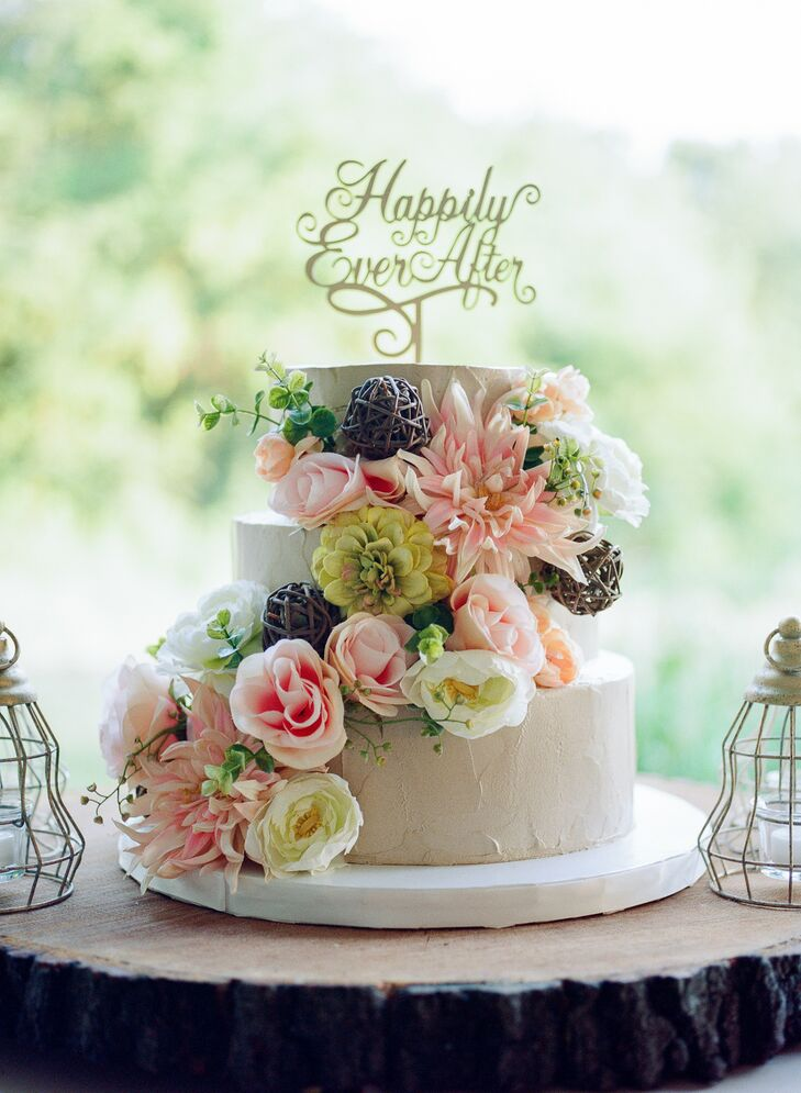 """The cannoli wedding cake was decorated in cascading blush and ivory flowers and a gold """"Happily ever after"""" cake topper."""