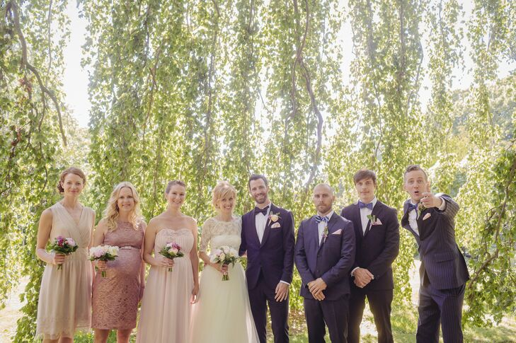 Linda's bridesmaids wore dresses of their choice in shades of blush and carried small pink bouquets. The groomsmen wore their own navy suits and blue bow ties.