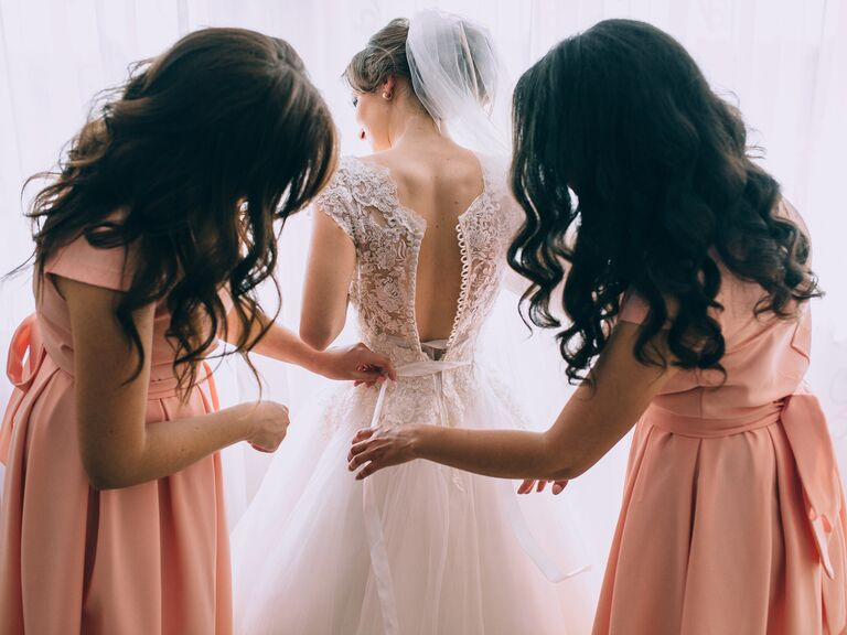 bridemaids helping the bride get into wedding dress