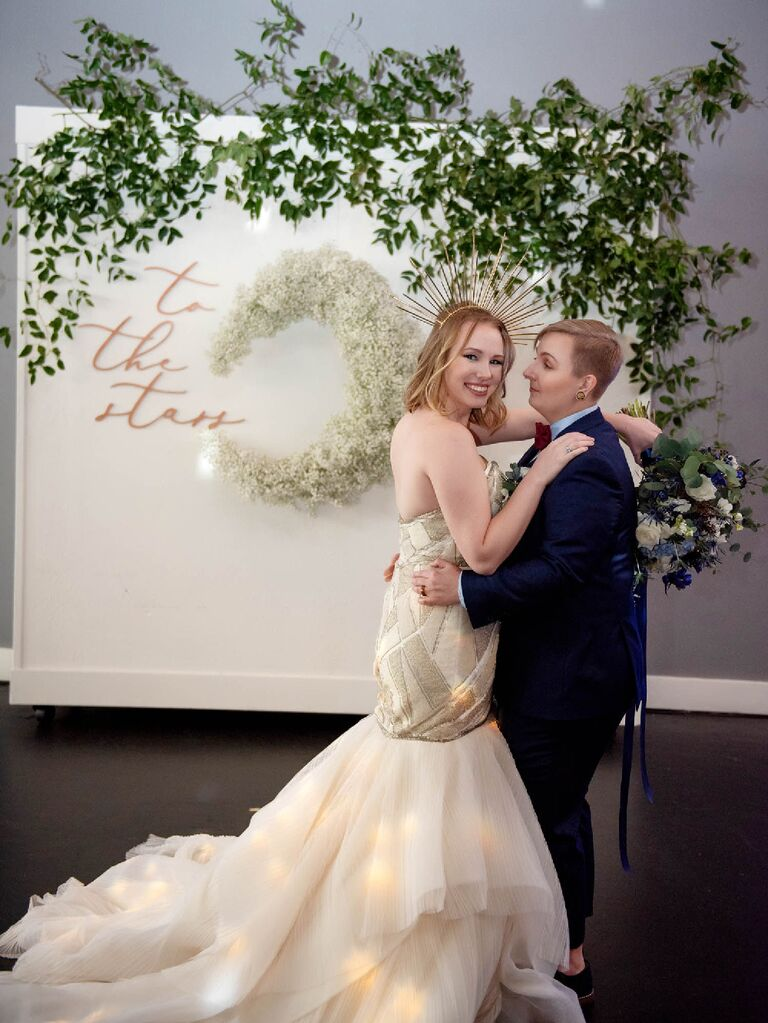 """Couple posing in front of """"To The Stars"""" celestial wedding sign"""