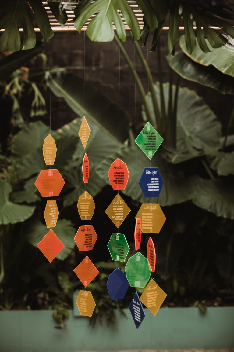 Colorful acrylic shapes hanging as part of a seating chart