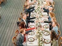 Guests toasting during dinner at wedding reception