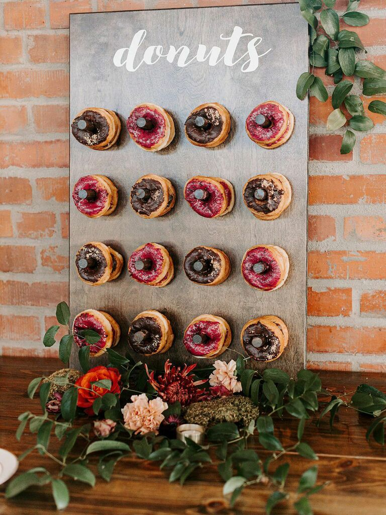 Donut wall with greenery accents at rustic wedding reception