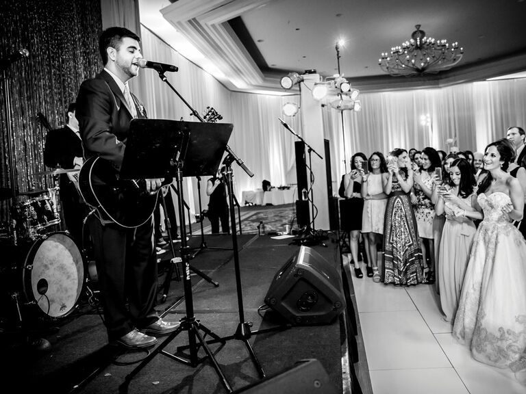 groom performing song during reception